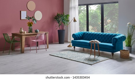 Modern living room blue sofa armchair, dinning table wooden and metal green chair.
