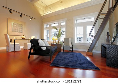 Modern living room with brick painted wall, high ceiling, hardwood floor and iron steep stairs. Furnished with classic elegant furniture