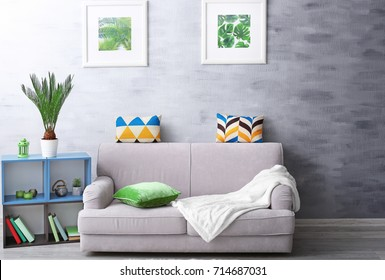 Modern living room design with framed pictures of tropical leaves and sago palm