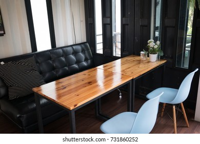 Modern living room. Designed for coffee shop, black leather sofa, blue chair and wood table.