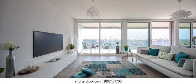 Modern living room with designer furniture. Sofa with light cushions and balcony view. Nobody inside. Frontal view, panorama - Shutterstock ID 1802457700