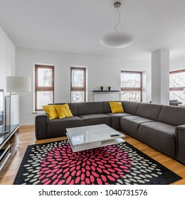 Modern living room with extra large sofa, coffee table and pattern carpet