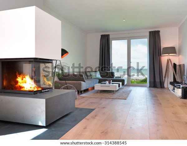 salon moderne avec cheminée et vue sur la mer