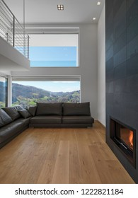 modern living room in the foreground the fireplace and the brown leather sofa the floor is made of hardwood