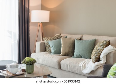 modernes Wohnzimmer mit grünen Kissen auf gemütlichem Sofa und Holzlampe, Inneneinrichtung
