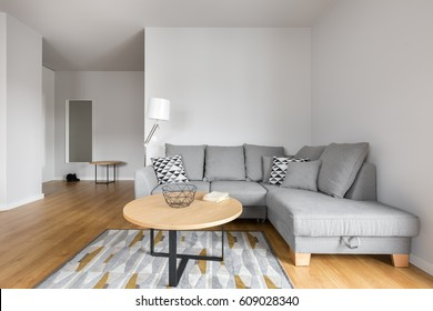 Modern living room with grey sofa with decorative pillows and small round table