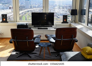 Modern living room interior with designer rose wood and leather furniture, flat screen TV, high quality surround audio system combined with speakers, sub woofer and vinyl record player during daylight