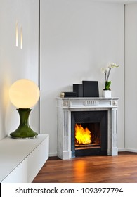 modern living room interior in the foreground the ancient fireplace and a old table lamp the floor is made of parquet floor