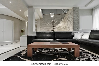 modern living room interior in the foreground the wooden coffeee table and the black leather sofa on the background the staircase and the stone wall