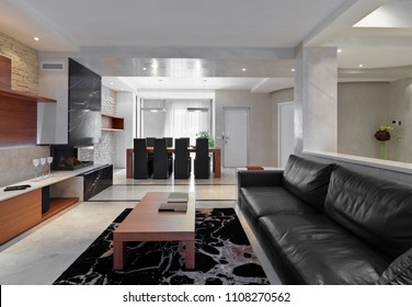 modern living room interior in the foreground the black leather sofas and coffee table on the background the wooden dining table and the fireplace with coating of black marble