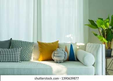 Modern living room interior with yellow pillow on it and green plant pot beside white sofa.