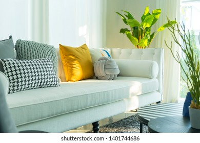 Modern living room interior with yellow pillow on white sofa.
