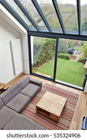 Modern living room with large windows and view on a autumnall garden