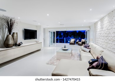 Modern living room at night with sofas and pillows next to fancy decorative items