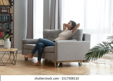 In modern living room peaceful african woman resting leaned on sofa closed eyes put hands behind head feels placidity enjoy weekend or vacation, inner harmony, no stress anxiety fatigue relief concept