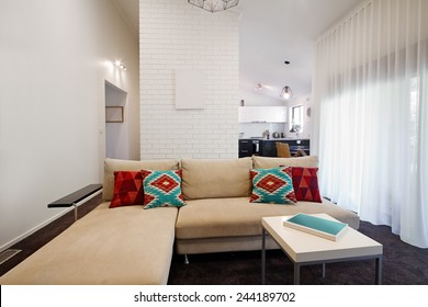 Modern living room sofa and coffee table with kitchen in background