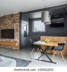 Modern living room with table and open, gray kitchen