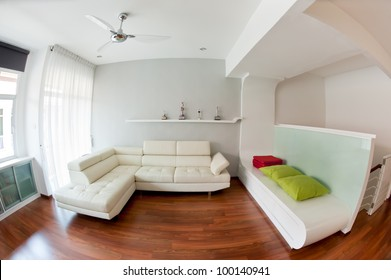 Modern living room with white sofa, wooden floor and golf trophy on the rack. Photo taken with fisheye lens