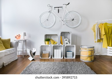 Modern living room with white stylish bicycle hanging on wall