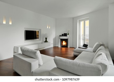 modern living room with wooden floor in the foregound a big fabric sofa on the background the ancient fireplace also on the wall in front of the sofa the led television