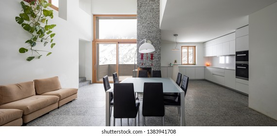 Modern livingroom with granite floor and wide windows. Snow and mountains view.
