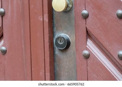 Modern lock of an old red wooden door