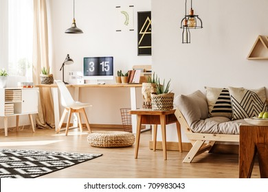 Modern loft interior full of natural wooden furniture and accessories with desk, computer, white chest, beige sofa, table and paper pots for plants