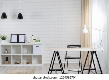 Modern loft interior with white brickwall, lamp, shelf, pictures, plants and some decoration and table with lamp and candles
