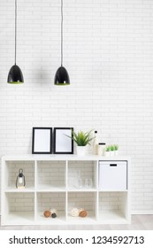 Modern loft interior with white brickwall, lamp, shelf, pictures, plants and some decoration / vertical shot