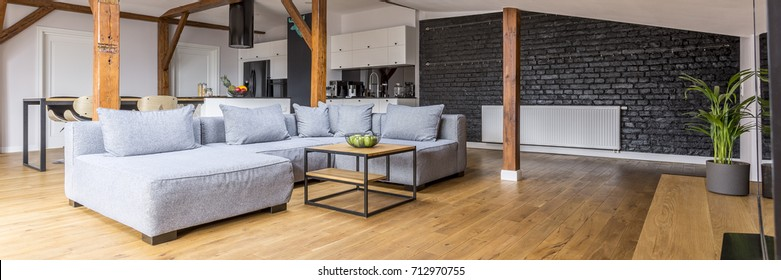 Modern loft open space apartment with wooden beams and floor, simple modern furniture, gray sofa, coffee table, brick wall, view from the living room