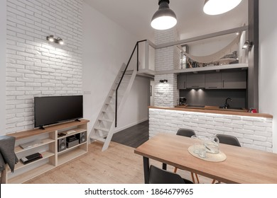 Modern loft style apartment with mezzanine, white brick on the walls and white stairs