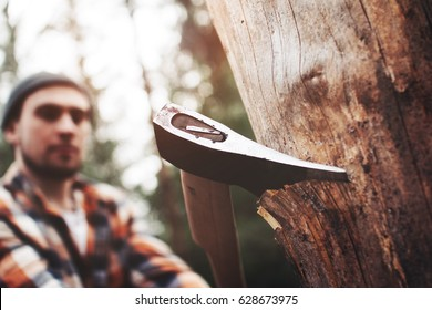 Modern logger in a plaid shirt with an ax chopping wood