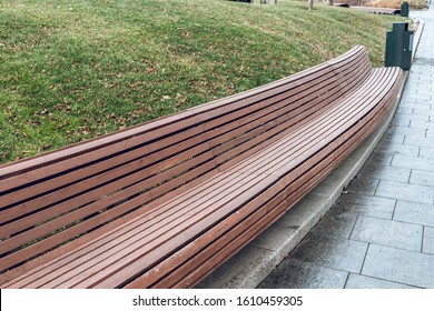 Modern long wooden bench in the park. Design of urban public space. The landscape park.