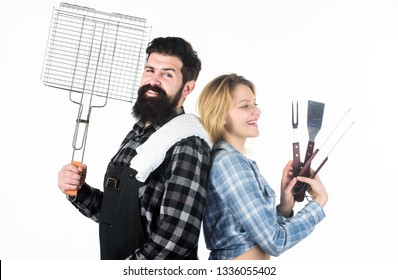 A modern looking compact BBQ. Couple having grill grid for grilling. Grilling is a healthy way of cooking food. Family gathering with grilling mangal. Bearded man and cute girl holding grilling grate.
