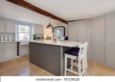 Modern looking kitchen with marble top island breakfast bar decorated in a contempoary style, built in appliances, traditional sink with fawcet tap, beamed ceiling, cupboards and draws.