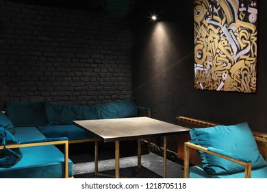 Modern lounge bar interior.Dark tone.Dark cyan sofa and chairs.Golden laterns in form of tubes.