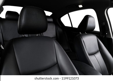 Modern luxury car black leather interior. Part of leather car seat details with stitching. Interior of prestige modern car. Comfortable perforated leather seat. Black perforated leather. Car detailing
