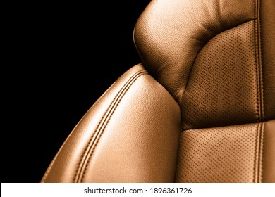 Modern luxury car brown leather interior. Part of orange perforated leather car seat details with white stitching. Interior of prestige car. Comfortable perforated leather seats. Perforated leather.