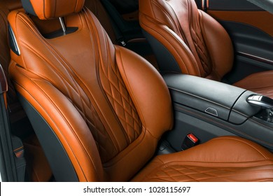 Modern Luxury car inside. Interior of prestige modern car. Comfortable leather brown seats. Orange perforated leather cockpit with isolated Black background. Modern car interior details