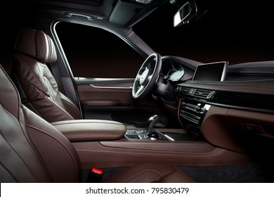 Modern luxury car Interior - steering wheel, shift lever and dashboard. Car interior luxury. Beige comfortable seats, steering wheel, dashboard, speedometer, display. Brown perforated leather.