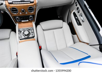 Modern luxury car white leather interior with natural wood panel. Part of leather seat details with stitching. Interior of prestige modern car. White perforated leather. Car detailing. Car inside