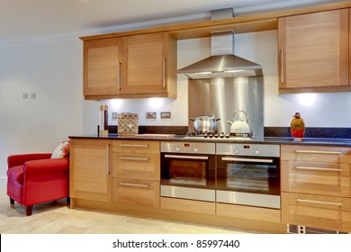 Modern luxury fitted kitchen with built in appliances, hob, stainless steel extractor hood and granite work surfaces
