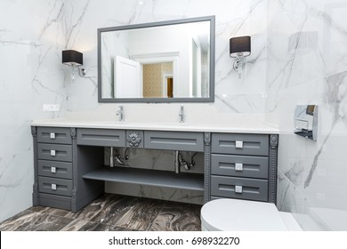 Modern luxury gray bathroom with two sink and shower tiled with white and brown marble tiles