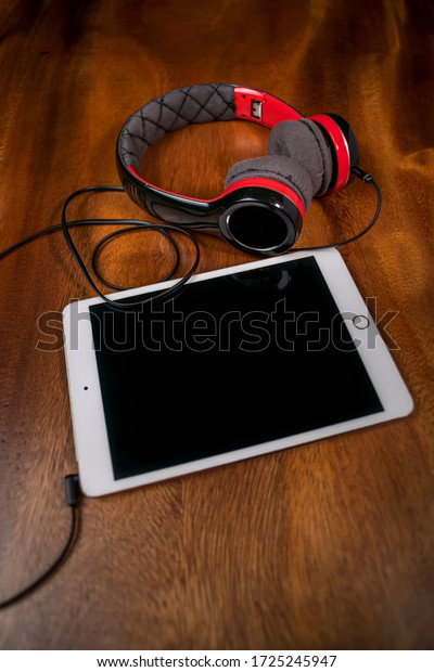 Modern luxury headphone with tablet foreground on wooden table