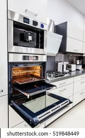 Modern luxury hi-tek black and white kitchen, clean interior design, focu at oven with door open