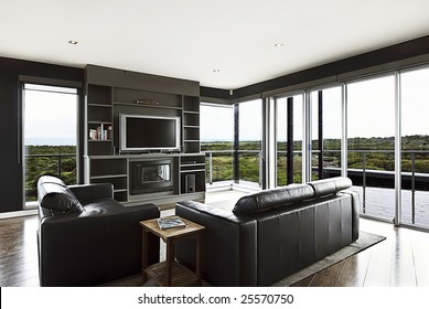 A modern luxury home interior living area with couch and flat screen TV and a beautiful view.