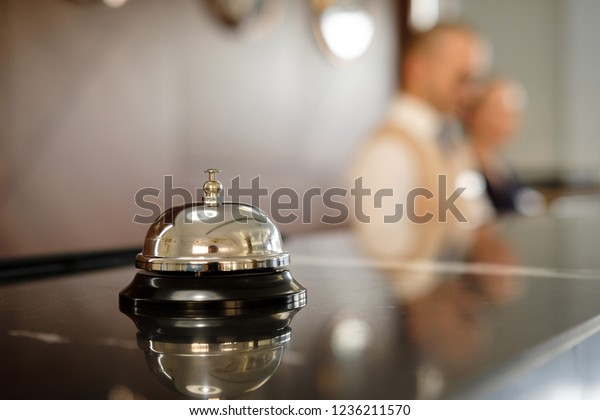 Modern luxury Hotel Reception Counter desk with Bell. Service Bell locating at reception. Silver Call Bell on table, Receptionists on background. Сheck in hotel. Concept.