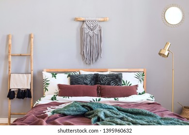 Modern and luxury interior of bedroom with design furnitures, stylish macrame, wooden ladder, gold lamp and elegant accessories. Beautiful bed sheets, blankets and pillows. Warm stylish home decor.