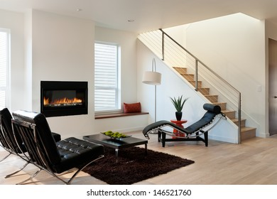 Modern Luxury Living Room/Horizontal shot of a modern living room in an upscale home with lounge chairs, and a view of stairs and fireplace.