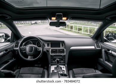 Modern luxury prestige car interior, dashboard, steering wheel. Black leather interior.